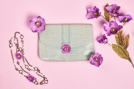 Summer Fashion Dames, accessoires. Glamour creatief handtas clutch, bloemen, halsband. Focus op pastelkleuren. Ongebruikelijke moderne elegante essentials, minimalisme. Overhead, bovenaanzicht, roze achtergrond Stockfoto