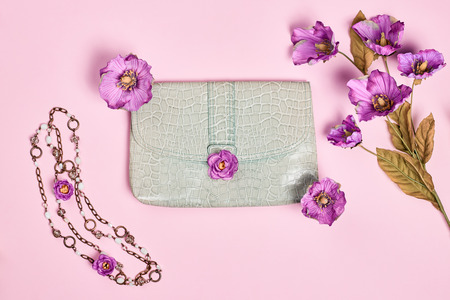 Summer Fashion Ladies, accessories. Glamor creative  handbag clutch, flowers, necklace. Focus on Pastel Colors. Unusual modern elegant essentials, minimalism. Overhead, top view, pink background Imagens