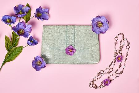 spring green: Summer Fashion Ladies, accessories. Glamor creative  handbag clutch, flowers, necklace. Focus on Pastel Colors. Unusual modern elegant essentials, minimalism. Overhead, top view, pink background Stock Photo