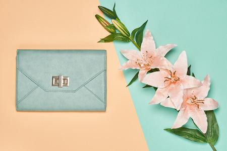 zestaw akcesoriów mody kobieta. Glamour stylowe torebki sprzęgło i lato lilia kwiaty. Elegancki modny dziewczyna. Niezwykłe twórcze spojrzenie. Overhead, romantyczny. Widok z góry, wanilia pastelowe tło