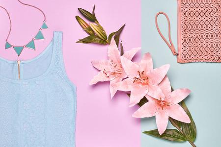 Glamour kanten jurk, stijlvolle handtas clutch, ketting, lelie bloemen. Zomer mode Dames kleding accessoires set. Ongebruikelijke creatieve elegante uitstraling. Overhead, romantische outfit. Bovenaanzicht, blauwe achtergrond Stockfoto