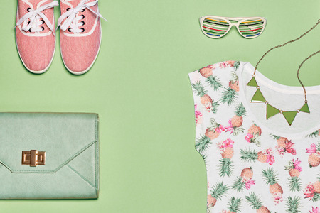 Summer Fashion girl clothes set, accessories. Creative hipster pastel colors. Stylish gumshoes, trendy dress, handbag clutch, necklace sunglasses. Unusual modern. Overhead, top view, green background Banco de Imagens