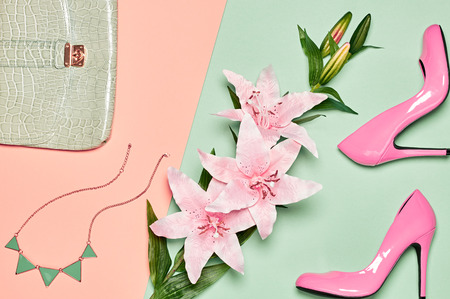 Fashion woman accessories set. Glamor luxury shoes heels, stylish handbag clutch, necklace, summer lily flowers. Elegant, unusual creative look. Overhead, romantic. Top view, vanilla pastel background