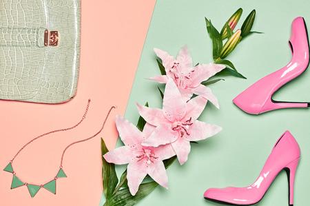 Moda akcesoria kobiety zestaw. Eleganckie buty obcasów luksusowych, stylowe sprzęgło torebki, naszyjnik, lilie letnie. Elegancki, nietypowy wygląd. Nad głową, romantycznie. Widok z góry, wanilii pastelowych tła