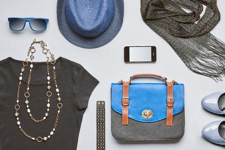 Mode vrouw kleding accessoires. Creative hipster, stijlvolle handtas, smartphone, zwarte top glamour schoenen trendy ketting blauwe hoed en sunglasses.Urban zomer outfit. Overhead, bovenaanzicht grijze achtergrond Stockfoto