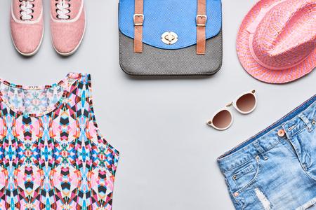 Street Style Mode dirl kleding accessoires set. Hipster vrouw, trendy handtas, top, denim, gumshoes, roze hoed en zonnebril. Bright stedelijke creatieve outfit. Overhead, bovenaanzicht op een grijze achtergrond