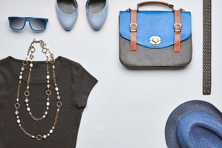 Fashion woman clothes accessories set. Creative hipster, stylish handbag, black top glamor shoes trendy necklace blue hat and sunglasses.Unusual urban summer outfit. Overhead, top view gray background