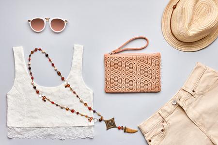 Zomer mode meisje kleding set, accessoires. Creatieve stedelijke hipster pastel kleuren. Stijlvolle kanten top, trendy zonnebril, handtas clutch, ketting, beige hoed. Ongebruikelijke modern. Boven, bovenaanzicht op grijs