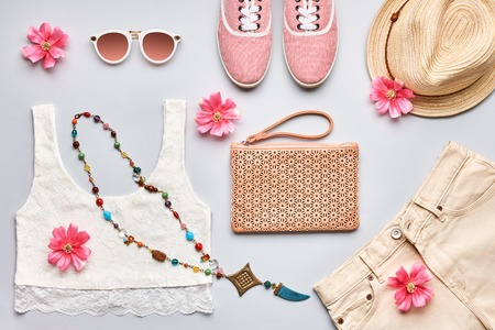 Summer Fashion girl clothes set, accessories. Trendy sunglasses, gumshoes, lace top, handbag clutch, necklace hat, flowers. Romantic style. Creative urban pastel colors. Overhead, top view on gray