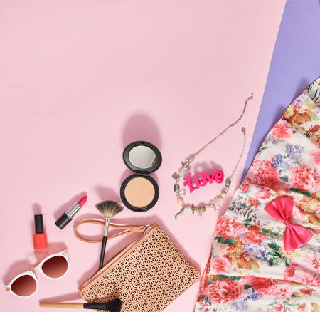 Fashion summer girl clothes accessories set. Woman essentials. Cosmetics, makeup. Stylish beige handbag clutch, trendy dress, necklace, sunglasses . Unusual overhead outfit, top view on pink