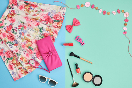 Fashion summer girl clothes accessories set. Woman essentials. Cosmetics, makeup. Stylish pink handbag clutch, trendy dress, necklace, sunglasses . Unusual overhead outfit, top view on blue