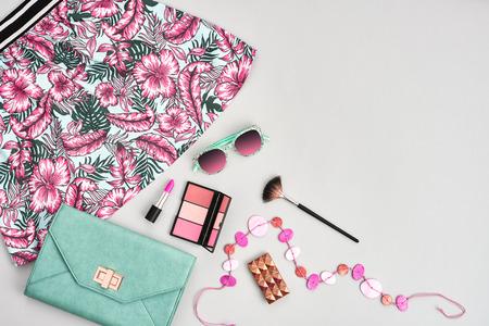 Mode stedelijke zomer outfit, meisje kleding set, cosmetica, make-up accessoires. Stijlvolle handtas clutch, trendy roze jurk, ketting, zonnebril. Belangrijkste vrouw. Ongewone overhead, bovenaanzicht op grijs