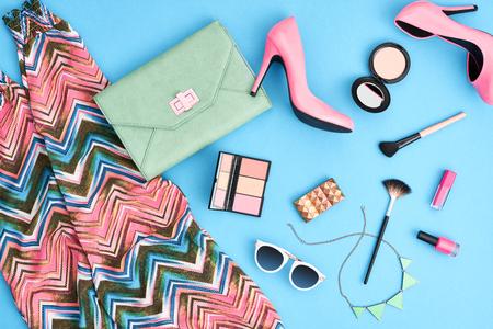 Moda stylowe ubrania, kosmetyki, akcesoria do makijażu. Miejskie lato dziewczynka kolorowy strój. Stylowe obcasy glamour, torebka sprzęgło, modne spodnie, naszyjnik okulary. Essentials kobiety. Niezwykłe, widok z góry Zdjęcie Seryjne