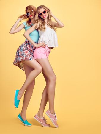 패션 hipster 여자 세련 된 여름 복장 재미입니다. 쾌활 한 자매 친구 미친 건 방진 감정. 유행 패션 선글라스, 매력적인 노란색 물결 모양의 헤어 스타일