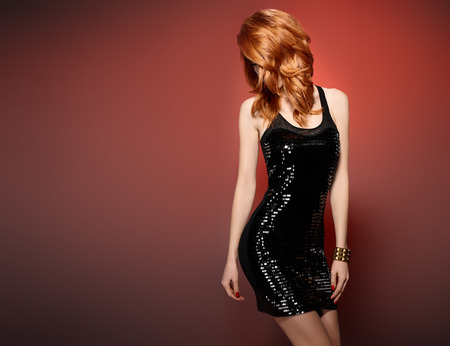 party outfit: Fashion woman in Glamour Sequin black dress. Stylish Luxury party Outfit. Playful redhead sexy Model girl, Trendy wavy Hairstyle on red. Fashion Makeup, shiny Accessories. Unusual creative
