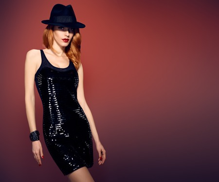 party outfit: Fashion woman in Glamour Sequin black dress. Stylish Luxury party Outfit. Playful redhead sexy Model girl in hat, Trendy wavy Hairstyle on red. Fashion Makeup, shiny Accessories. Unusual creative