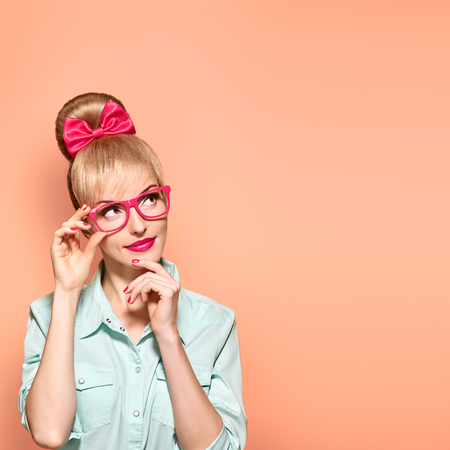 Fashion. Woman in Stylish Glasses Having Fun. Hipster fashion girl think, idea. Playful nerd Blonde with Glamour Pinup Stylish hairstyle, Trendy fashion, red bow Makeup. Unusual Creative, on yellow Stock Photo