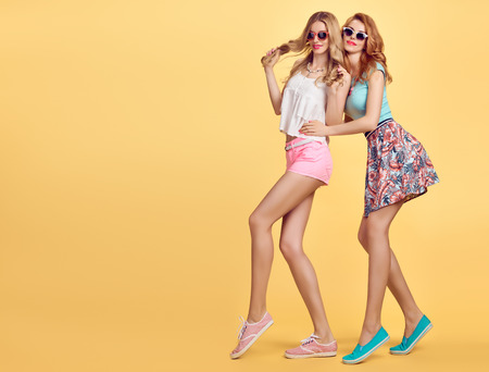party outfit: Fashion Hipster woman in Stylish Summer Outfit Having fun. Hipster sisters friends crazy cheeky emotions.Girl in Fashion sunglasses,Glamour hairstyle posing on yellow.Unusual Creative