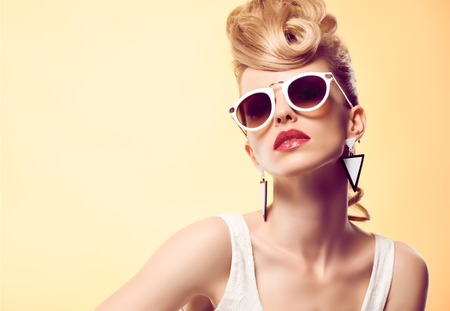 Fashion portrait Hipster Model woman, Stylish hairstyle. Fashion Makeup. Blond sexy Model, Trendy Glamour sunglasses. Playful girl cheeky emotion. Unusual Creative.Party disco mohawk hairstyle Banco de Imagens