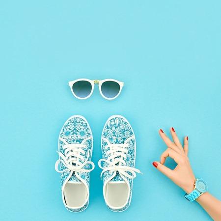 Mode. Kledingaccessoires mode-set. Vrouwelijke hand OK gebaar en stijlvolle trendy gumshoes, Glamour zonnebril. Zomer mode meisje Outfit, accessoires. Hipster Essentials. Minimale mode-stijl