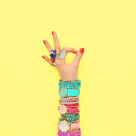 Fashion. Accessories fashion Set. Female hand OK Gesture Stylish Trendy Wrist Watches, Glamor bracelets and rings. Summer fashion girl Outfit, accessories. Hipster Essentials. Minimal fashion style