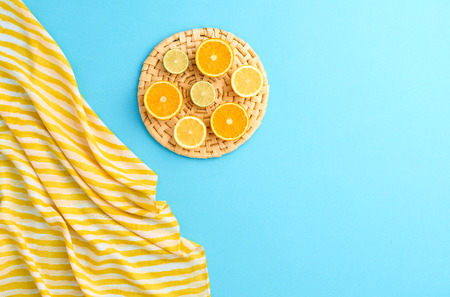 minimal: Fashion. Summer Beach set. Tropical Fruit Citrus, Orange, Lime. Bright Summer Color. Essentials creative art. Minimal concept. Top view. Yellow blue background