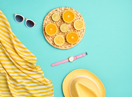 oncept: Fashion. Summer Beach set. Tropical Fruit Citrus, Orange, Lime. Bright Summer Color. Stylish woman Sunglasses, Trendy hat. Essentials creative art. Minimal concept. Top view. Yellow blue background