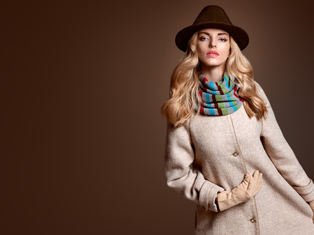 Fall Fashion. Model Woman in Autumn Fashion Outfit, Stylish Coat Trendy Hat, in Scarf, Gloves. Fashion Makeup. Playful Blonde girl with Wavy hair. Fall Autumn Winter. Fashion Pose. Creative Vintage Stock Photo