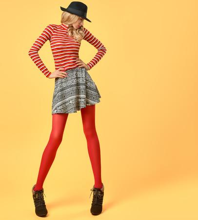 秋のファッション。秋のファッションの服のモデルの女性。スタイリッシュなセーター赤ファッションのストッキングでトレンディな帽子。長い脚 写真素材