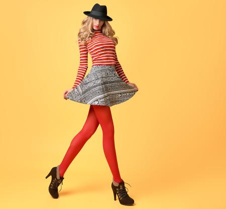 秋のファッション。楽しい秋のファッションの服のモデルの女性。スタイリッシュなセーター赤ファッションのストッキングでトレンディな帽子。