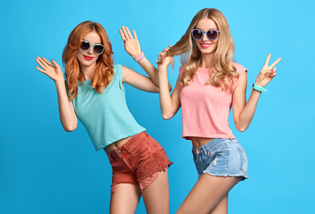 Fashion Hipster vrouw plezier Crazy Cheeky Dance. Hipster Sisters Best Friends Tweelingen in Stijlvol Summer Outfit. Funny Girl Fashion Sunglasses.Glamour mode trendy kapsel, dancing.Creative