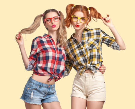 model fish: Fashion Hipster woman make Fish Face, Having Fun Crazy Cheeky. Hipster Sisters Best Friends. Nerd in fashion Trendy Plaid Shirt. Twins in Stylish Summer Outfit. Funny Model Girl Fashion Sunglasses Stock Photo