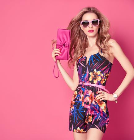 Adatti la donna in vestito alla moda primavera-estate. Elegante acconciatura ondulata, moda Occhiali da sole, estate floreale Outfit. Glamour Signora bionda sexy in tuta, posa di moda. Ragazza giocosa, l'estate di lusso rosa frizione Archivio Fotografico - 71166720