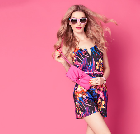 Fashion woman in Trendy Spring Summer Dress. Stylish wavy hairstyle, fashion Sunglasses, Summer Floral Outfit. Glamour Blond lady in Sexy Jumpsuit, fashion pose. Playful Girl,Luxury summer Pink Clutch Stok Fotoğraf - 71246334