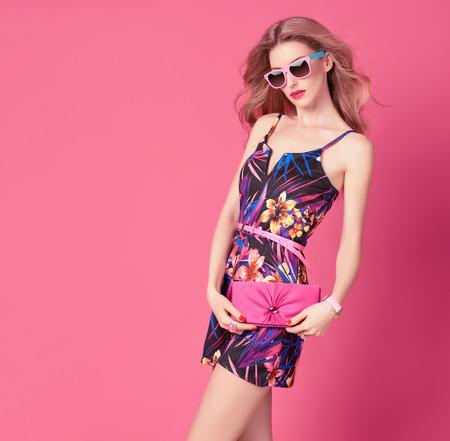 Mujer de moda en moda vestido de primavera y verano. peinado con estilo ondulado, gafas de sol de moda, verano floral traje. Glamour Señora rubia atractiva en el mono, actitud de la moda. Chica lúdica, verano rosado de lujo del embrague Foto de archivo - 71246331