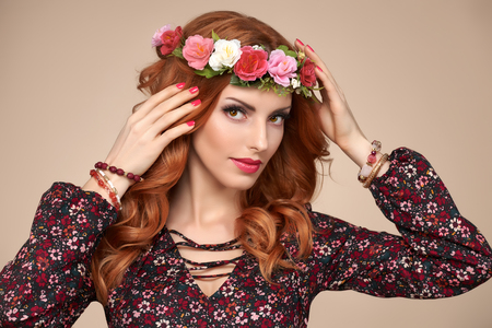 Beautiful Curly Redhead Portrait in Fashion Flower Wreath. Shiny Curly flower Volume Hairstyle. Happy Beauty Model Woman. Playful Glamour Sexy lady, fashion Makeup, Boho wreath, Trendy summer Dress