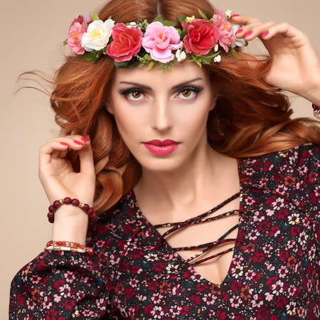 Beautiful Curly Redhead Portrait in Fashion Flower Wreath. Shiny Curly flower Volume Hairstyle. Happy Beauty Model Woman. Playful Glamour Confident Sexy lady, fashion Makeup, Boho wreath, Trendy Dress