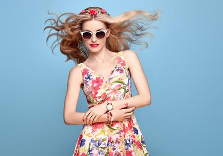 패션 뷰티. 패션에서 관능적 인 섹시 한 금발 모델 포즈 웃 고. 여름 의상을 입은 여자. 트렌디 한 꽃 드레스, 세련된 물결 모양의 헤어 스타일, 패션 플 스톡 콘텐츠