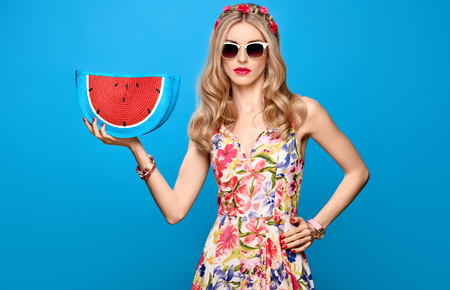 Fashion Beauty woman in Summer Outfit. Sensual Sexy Blond Model in fashion pose. Trendy Floral summer Dress, Glamour Clutch, Stylish wavy hairstyle, fashion Hairband. Playful Romantic summer Girl Stock Photo
