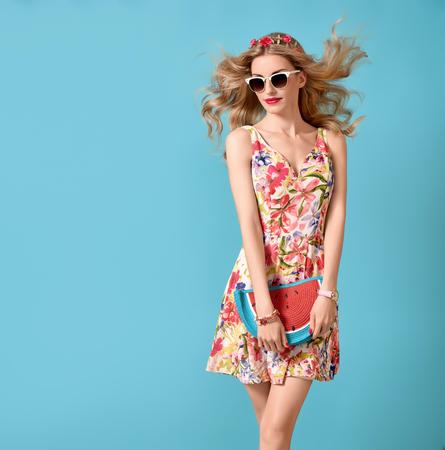 夏の服装でファッション美容女性。ファッションのポーズで官能的なセクシーなブロンドのモデル。トレンディな花夏ドレス、グラマー クラッチ ス