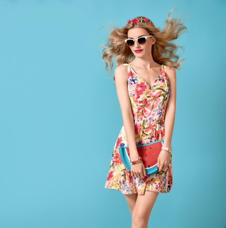 Fashion Beauty woman in Summer Outfit. Sensual Sexy Blond Model in fashion pose. Trendy Floral summer Dress, Glamour Clutch, Stylish wavy hairstyle, fashion Hairband. Playful Romantic summer Girl Zdjęcie Seryjne