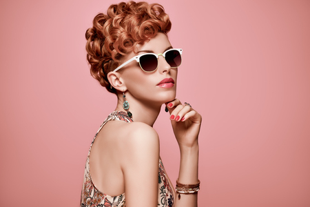 Fashion Portrait Model in Sexy Dress. Stylish Mohawk hairstyle,fashion Makeup.Beauty woman in Trendy Sunglasses,Glamour Redhead,fashion pose.Playful Girl,Luxury summer Accessories.Summer Floral Outfit Zdjęcie Seryjne
