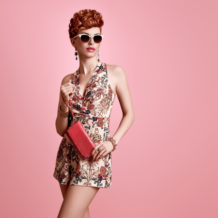 Fashion Model in Sexy Jumpsuit. Stylish Mohawk hairstyle. Beauty woman in Trendy Summer Dress, fashion Makeup, Summer Floral Outfit.Glamour Redhead,fashion pose. Playful Girl,Luxury summer Accessories