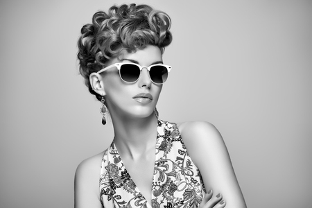 Fashion Portrait Model in Sexy Dress. Stylish Mohawk hairstyle,fashion Makeup. Beauty woman in Trendy Sunglasses, Glamour Lady,fashion pose. Playful Girl,Luxury summer Accessories.Black and white