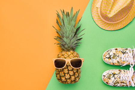 Fashion Hipster Pineapple Fruit. Bright Summer Color, Accessories. Tropical pineapple with Sunglasses, Stylish Hat Creative Art concept. Minimal style. Yellow summer party background