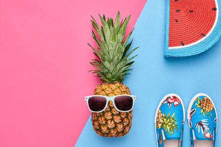 Fashion Hipster Pineapple Fruit. Bright Summer Color, Accessories. Tropical pineapple with Sunglasses, Stylish Glamour Handbag Creative Art concept. Minimal style. Pink blue summer party background