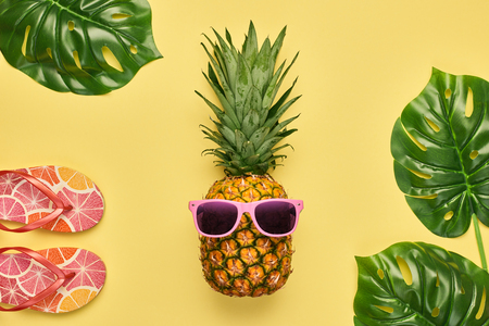 Fashion Pineapple. Bright Summer Color. Clothes Accessories set. Creative Art concept. Fashion woman Flip Flops, Tropical pineapple. Stylish girl. Minimal. Summer background on yellow. Top View