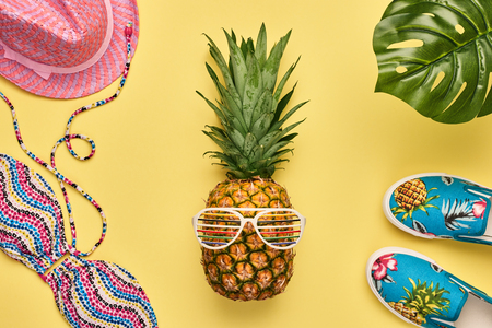 fashion art: Fashion Pineapple. Bright Summer Color. Clothes Accessories set. Creative Art concept. Fashion woman Swimsuit Bikini, Tropical pineapple. Stylish girl. Minimal. Summer background on yellow. Top View