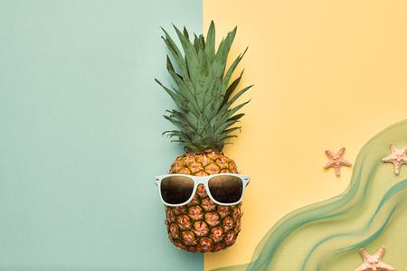 ファッションの流行に敏感なパイナップルの果実。明るい夏色アクセサリー。サングラスをかけたトロピカル パイナップル。創造的な芸術の概念。