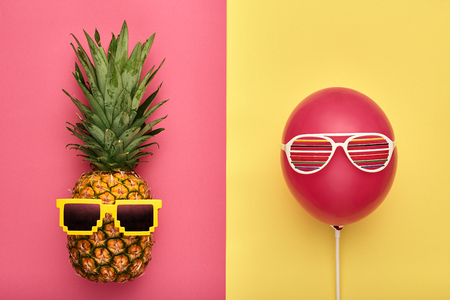 Fashion Pineapple and Pink air Balloon. Bright Summer Color, Accessories. Tropical Hipster pineapple with Sunglasses. Creative Art concept. Minimal style. Summer party background. Fun Banco de Imagens